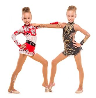 Irmãs gêmeas meninas em lindos fatos estão posando.