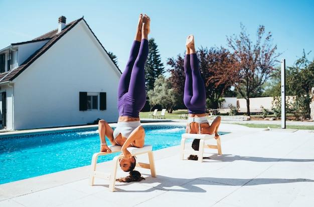 Irmãs gêmeas praticando ioga à beira da piscina.
