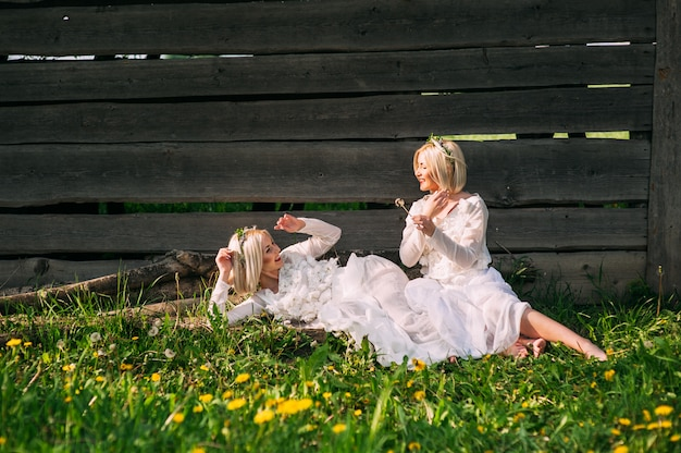 Irmãs gêmeas sentado em uma parede de madeira