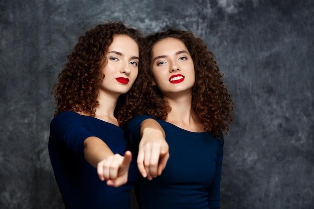 Irmãs gêmeas sorrindo apontando os dedos para a câmera em cinza