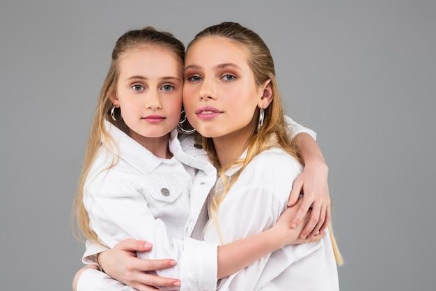 Irmãs jovens de cabelos compridos posando juntas em um fundo cinza usando as mesmas roupas elegantes