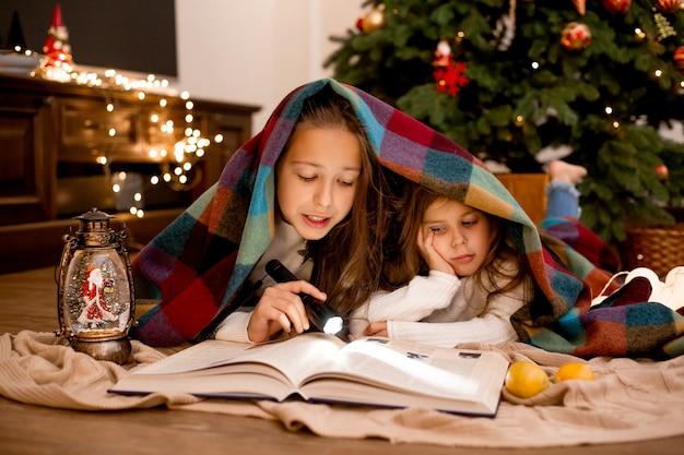 Irmãs lêem um livro embrulhado em xadrez