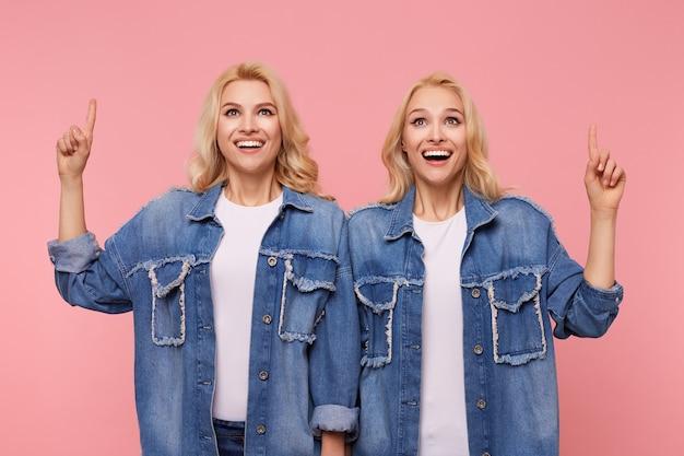 Irmãs loiras jovens e agitadas, vestidas com jaquetas jeans e camisetas brancas, mostrando-se animadamente para cima com os dedos indicadores levantados, de pé sobre um fundo rosa