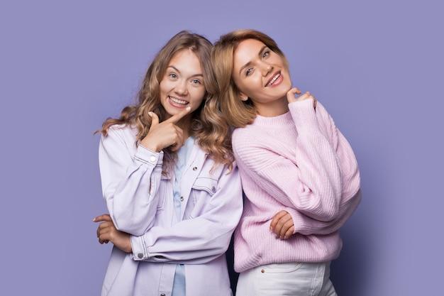 Irmãs loiras sorrindo para a câmera com roupas casuais tocando o queixo na parede violeta do estúdio
