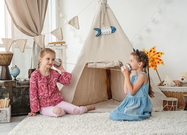 Irmãs mais novas brincando com um telefone caseiro feito de lata e linha na sala com cabana