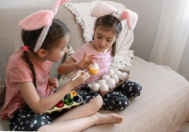 Irmãs mais novas com orelhas de coelho pintando ovos de páscoa no sofá em casa