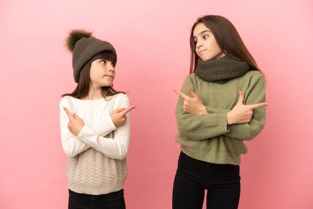 Irmãs mais novas com roupas de inverno isoladas em fundo rosa apontando para as laterais tendo dúvidas