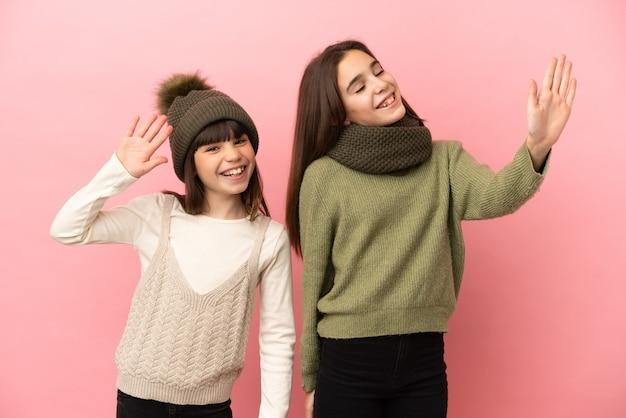 Irmãs mais novas com roupas de inverno isoladas em um fundo rosa saudando com a mão com expressão feliz