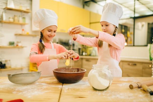 Irmãs mais novas cozinhando em bonés amassando ovos em um arco