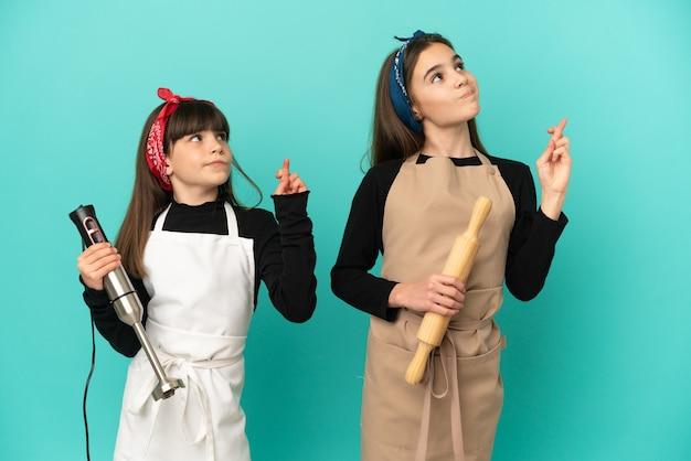 Irmãs mais novas cozinhando em casa isoladas em um fundo azul com os dedos se cruzando e desejando o melhor