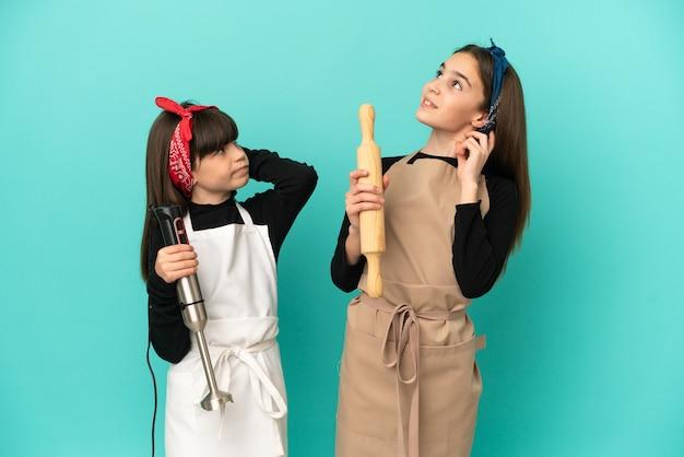 Irmãs mais novas cozinhando em casa isoladas em um fundo azul pensando uma ideia enquanto coçam a cabeça