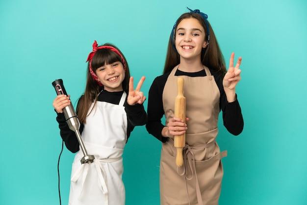 Irmãs mais novas cozinhando em casa isoladas em um fundo azul sorrindo e mostrando sinal de vitória