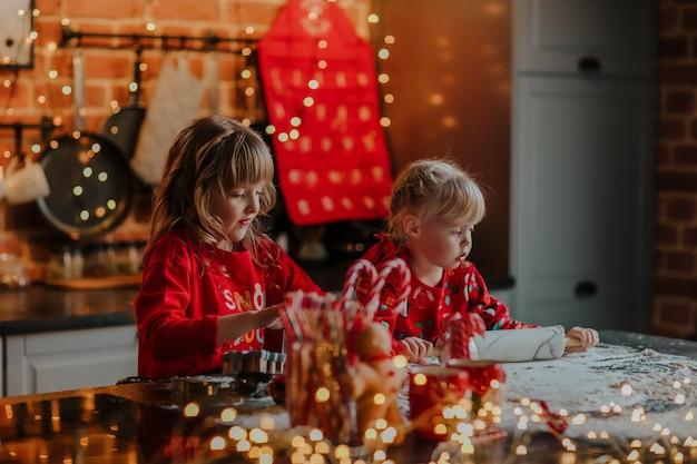 Irmãs mais novas enrolando a massa para os biscoitos de natal