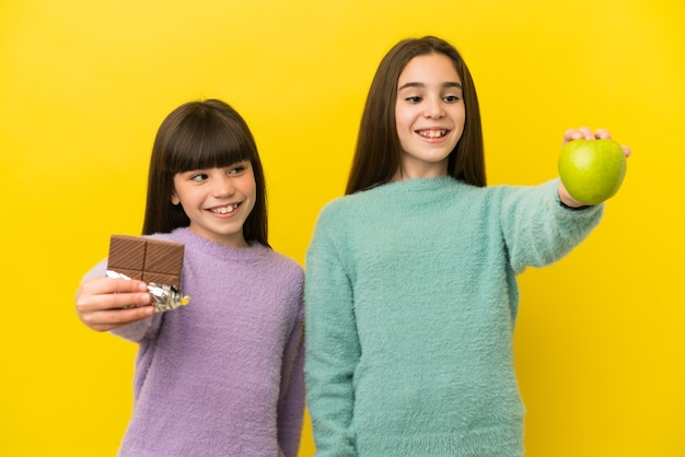 Irmãs mais novas isoladas em fundo amarelo pegando um comprimido de chocolate com uma das mãos e uma maçã com a outra