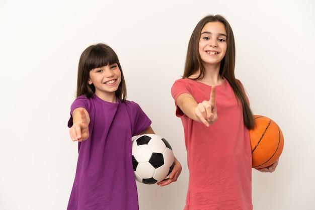 Irmãs mais novas jogando futebol e basquete isoladas, mostrando e levantando um dedo