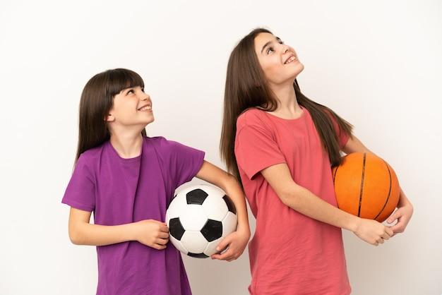 Irmãs mais novas jogando futebol e basquete isoladas no fundo branco, olhando para cima enquanto sorriem