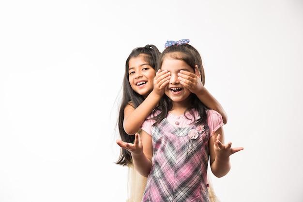 Irmãs mais novas ou amigas indianas ou asiáticas brincalhonas e bonitas, que se abraçam, dançam e se empurram. isolado sobre fundo branco