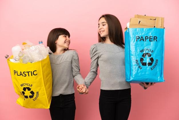 Irmãs mais novas reciclando papel e plástico isolados em um fundo rosa, aperto de mão após um bom negócio