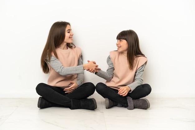 Irmãs mais novas sentadas no chão, isoladas no fundo branco, apertando a mão após um bom negócio