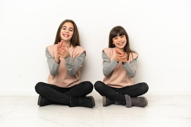 Irmãs mais novas sentadas no chão, isoladas no fundo branco, aplaudindo após a apresentação em uma conferência