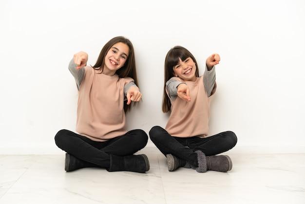 Irmãs mais novas sentadas no chão isoladas no fundo branco apontam o dedo para você enquanto sorriem