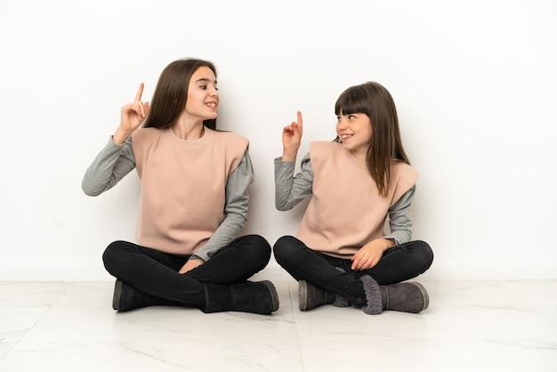 Irmãs mais novas sentadas no chão isoladas no fundo branco com a intenção de perceber a solução enquanto levantam um dedo