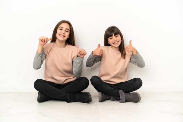 Irmãs mais novas sentadas no chão, isoladas no fundo branco, fazendo um gesto de polegar para cima com as duas mãos e sorrindo