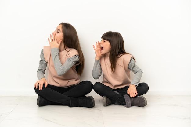 Irmãs mais novas sentadas no chão isoladas no fundo branco gritando com a boca bem aberta para o lado