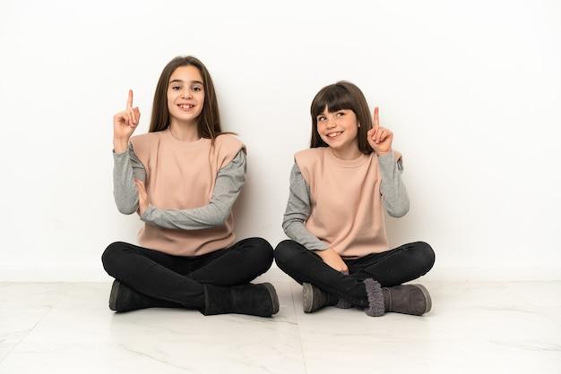 Irmãs mais novas sentadas no chão isoladas no fundo branco, mostrando e levantando um dedo em sinal dos melhores