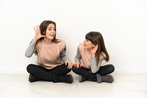 Irmãs mais novas sentadas no chão isoladas no fundo branco ouvindo alguma coisa colocando a mão na orelha
