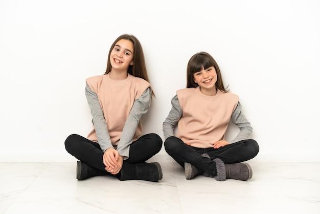 Irmãs mais novas sentadas no chão, isoladas no fundo branco, posando com os braços na cintura e sorrindo