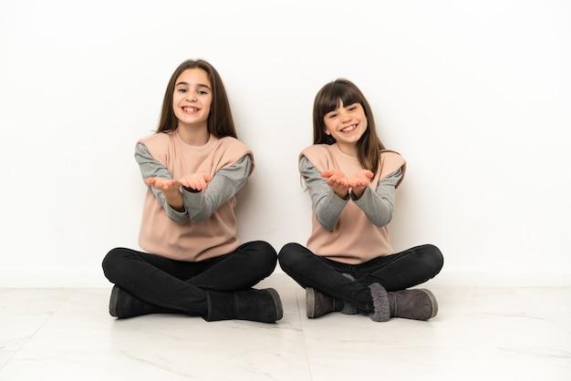 Irmãs mais novas sentadas no chão, isoladas no fundo branco, segurando o imaginário de copyspace na palma da mão para inserir um anúncio