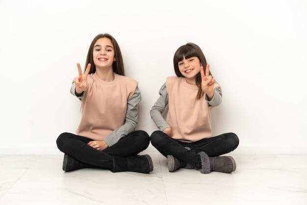 Irmãs mais novas sentadas no chão, isoladas no fundo branco, sorrindo e mostrando sinal de vitória