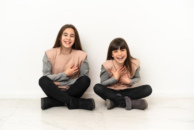 Irmãs mais novas sentadas no chão isoladas no fundo branco sorrindo muito enquanto colocam as mãos no peito