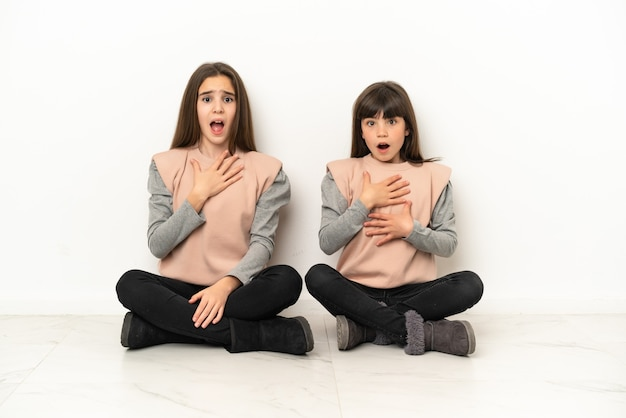 Irmãs mais novas sentadas no chão isoladas