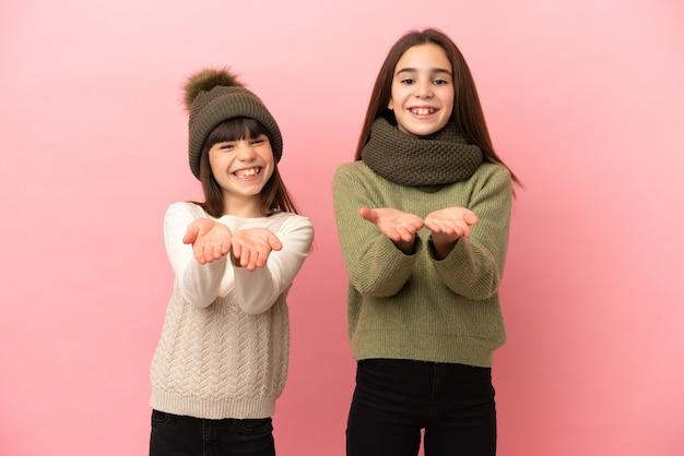Irmãs mais novas vestindo roupas de inverno isoladas em um fundo rosa, segurando o imaginário de copyspace na palma da mão para inserir um anúncio