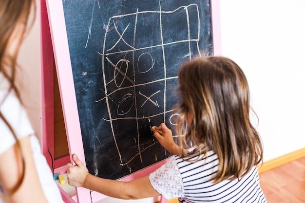 Irmãs meninas mais velhas e mais jovens jogam jogos no quadro-negro