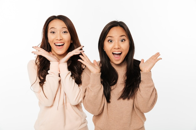 Irmãs muito chocadas asiáticas das senhoras