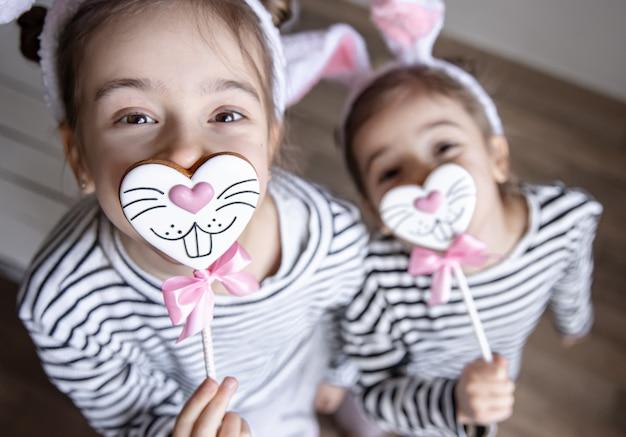 Irmãs pequenas engraçadas com biscoitos de páscoa em forma de carinhas de coelho e com orelhas de coelho.