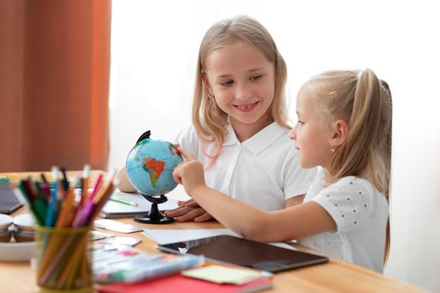 Irmãs pequenas fazendo escola online juntas em casa