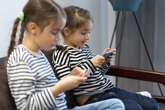 Irmãs pequenas fofas usam telefones enquanto estão sentadas no sofá em casa.
