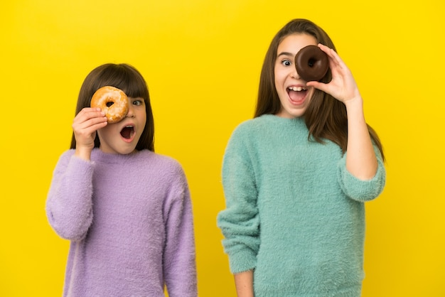 Irmãs pequenas isoladas em um fundo amarelo segurando rosquinhas em um olho