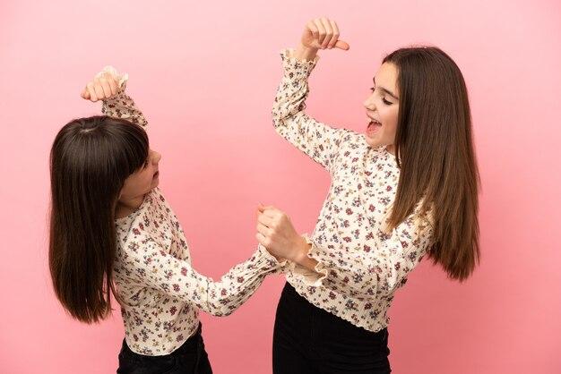 Irmãs pequenas isoladas em um fundo rosa comemorando a vitória na posição vencedora