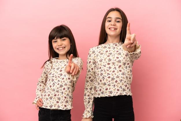 Irmãs pequenas isoladas em um fundo rosa, mostrando e levantando um dedo