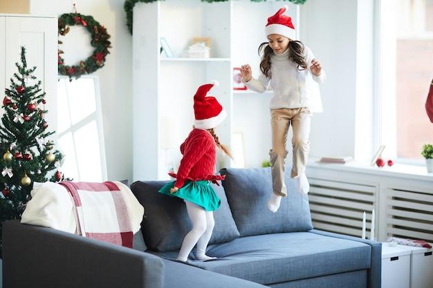 Irmãs pulando e brincando no sofá, meninas com chapéu de papai noel