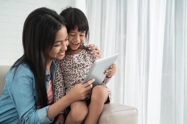 Irmãs, sentado num sofá e usando tablet