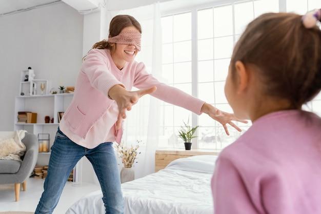 Irmãs sorridentes brincando em casa com os olhos vendados