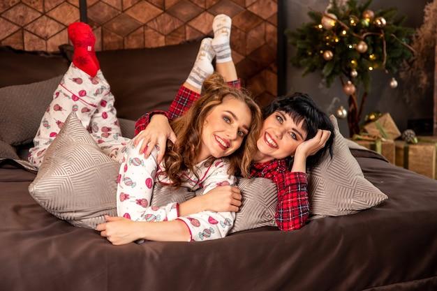 Irmãs sorrindo e celebrando a véspera de ano novo e o natal. existem presentes e ramos de abeto decorados com bolas douradas.