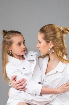 Irmãs tranquilas e elegantes olhando profundamente nos olhos enquanto sentam juntas no estúdio fotográfico