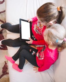 Irmãs usando tablet com tela em branco